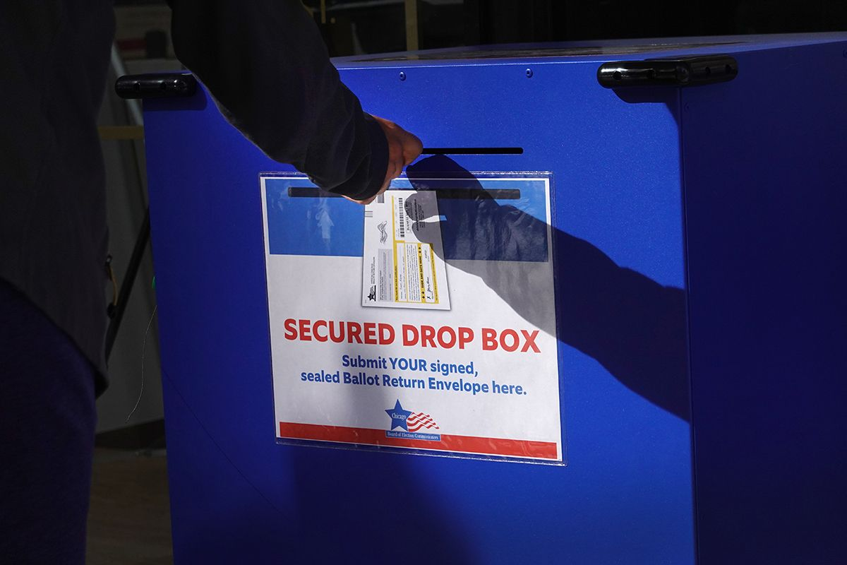 A resident drops off a vote-by-mail ballot in a secure drop box