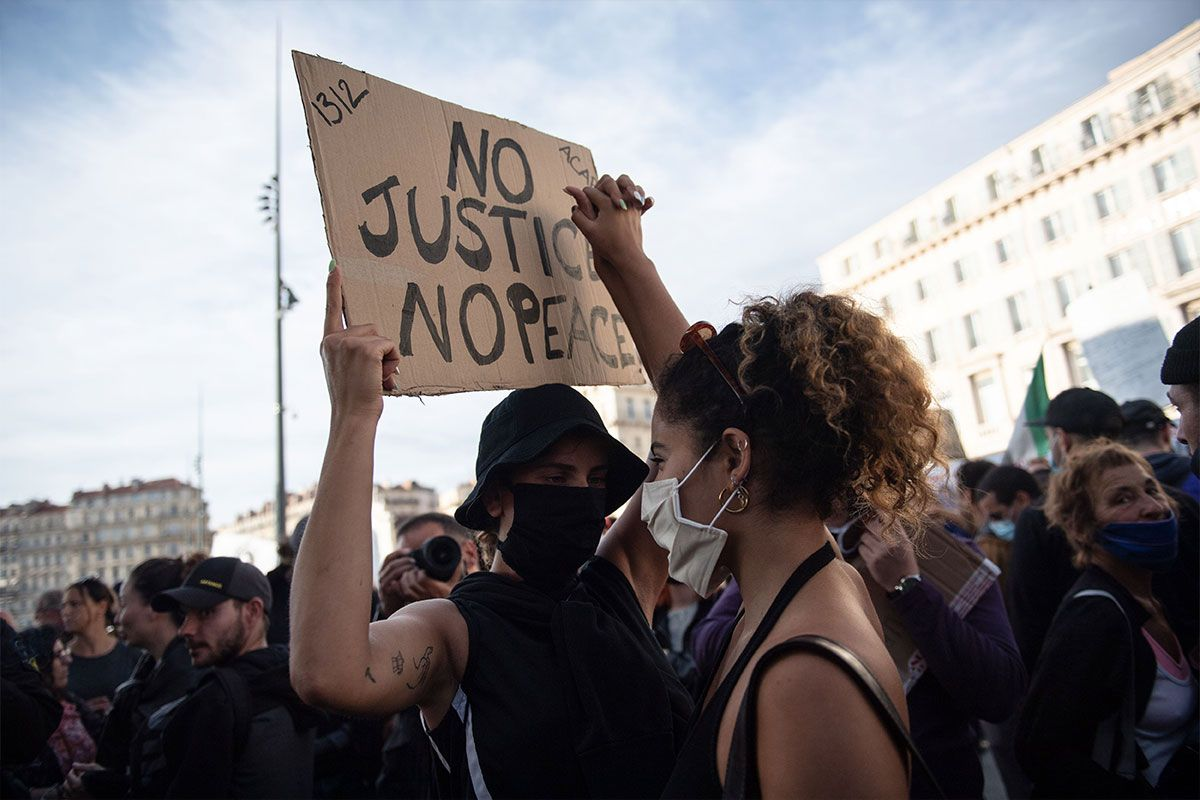 """protesters hold up """"no justice no peace"""" sign"""