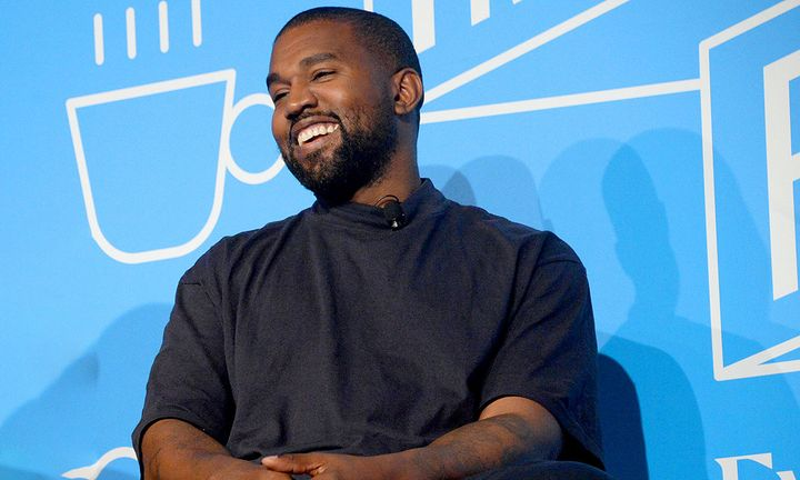 Kanye West smiling blue background