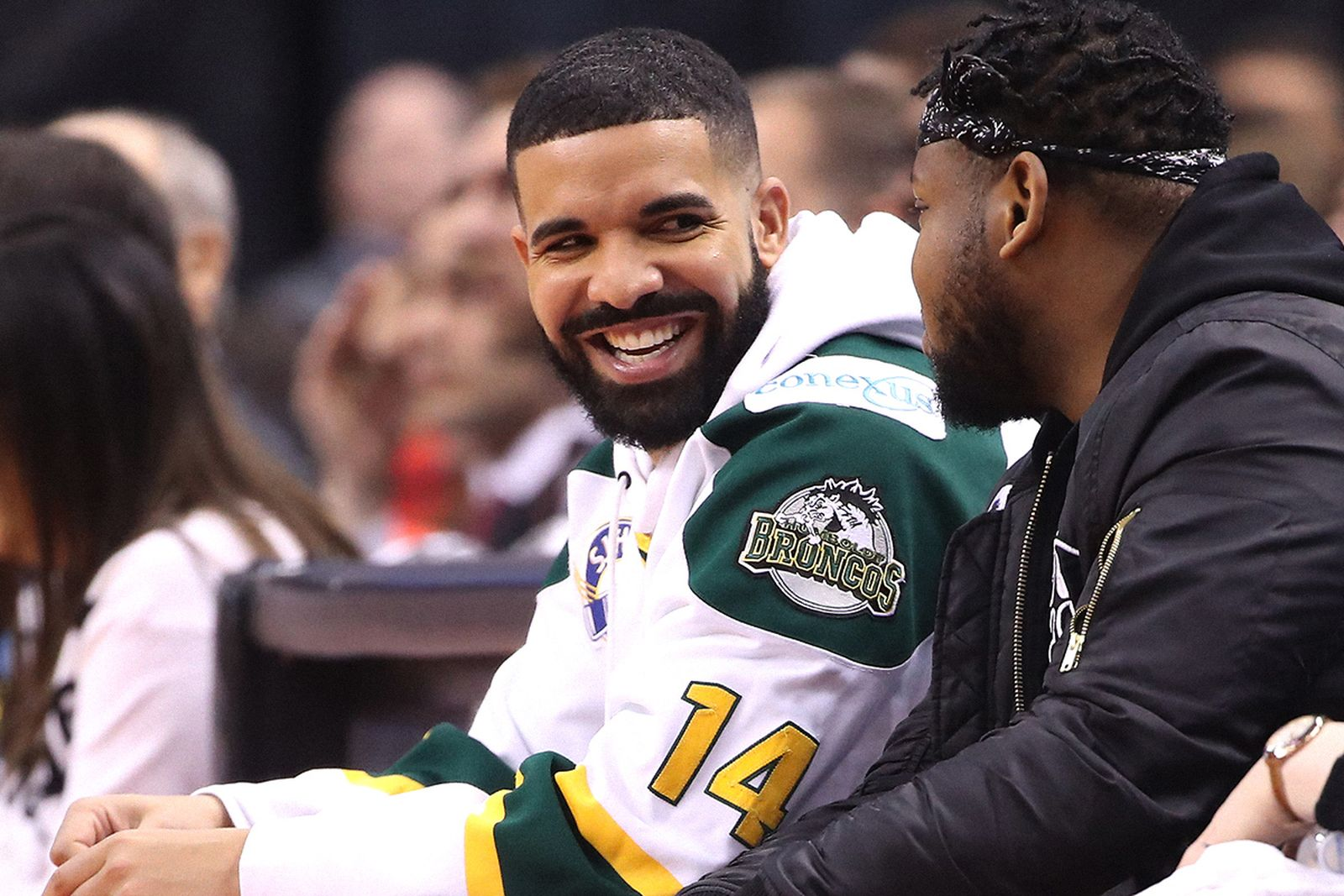 Rap artist Drake smiles as he wears a Humboldt Broncos jersey during the Toronto Raptors game against the Washington Wizards during Game One of the first round of the 2018 NBA Playoffs at Air Canada Centre on April 14, 2018 in Toronto, Canada.