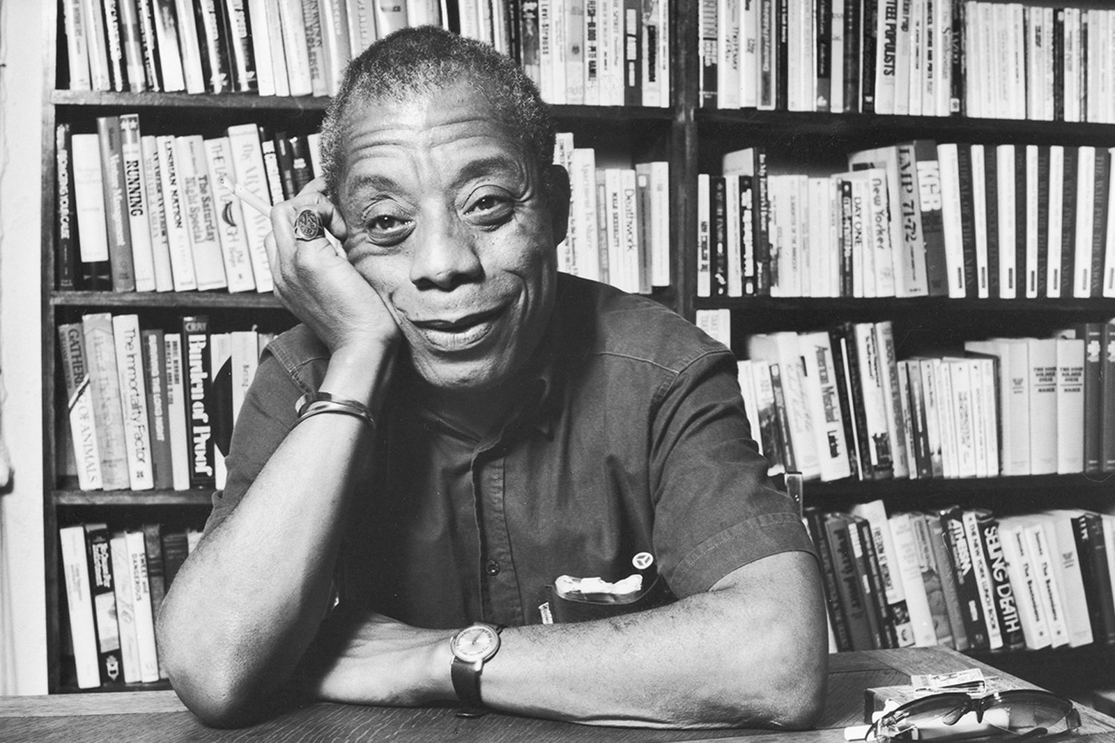 James Baldwin smiling in front of a book shelf