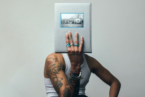 Cam Hicks covers face with For the Porch book