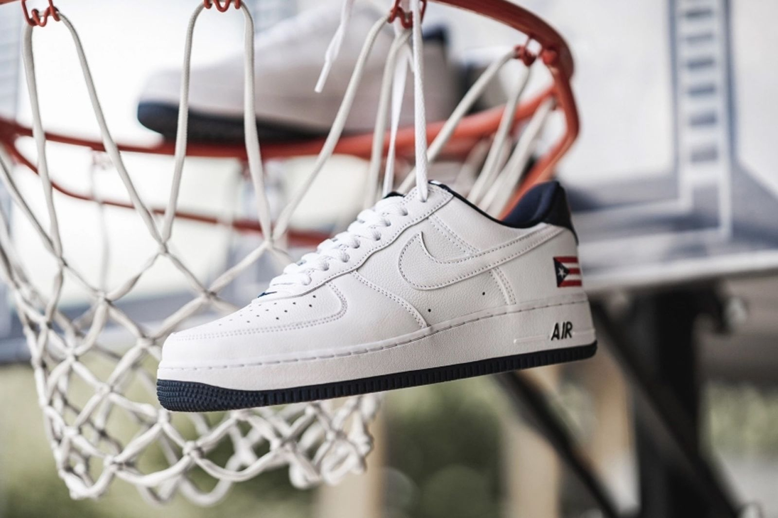 white leather Puerto Rico Nike Air Force 1 hanging in a basketball net