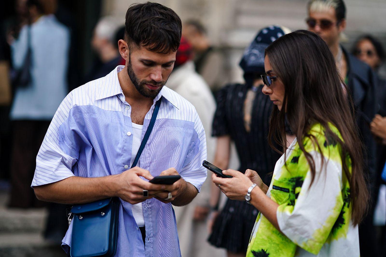 couple on their phones at Paris Fashion Week
