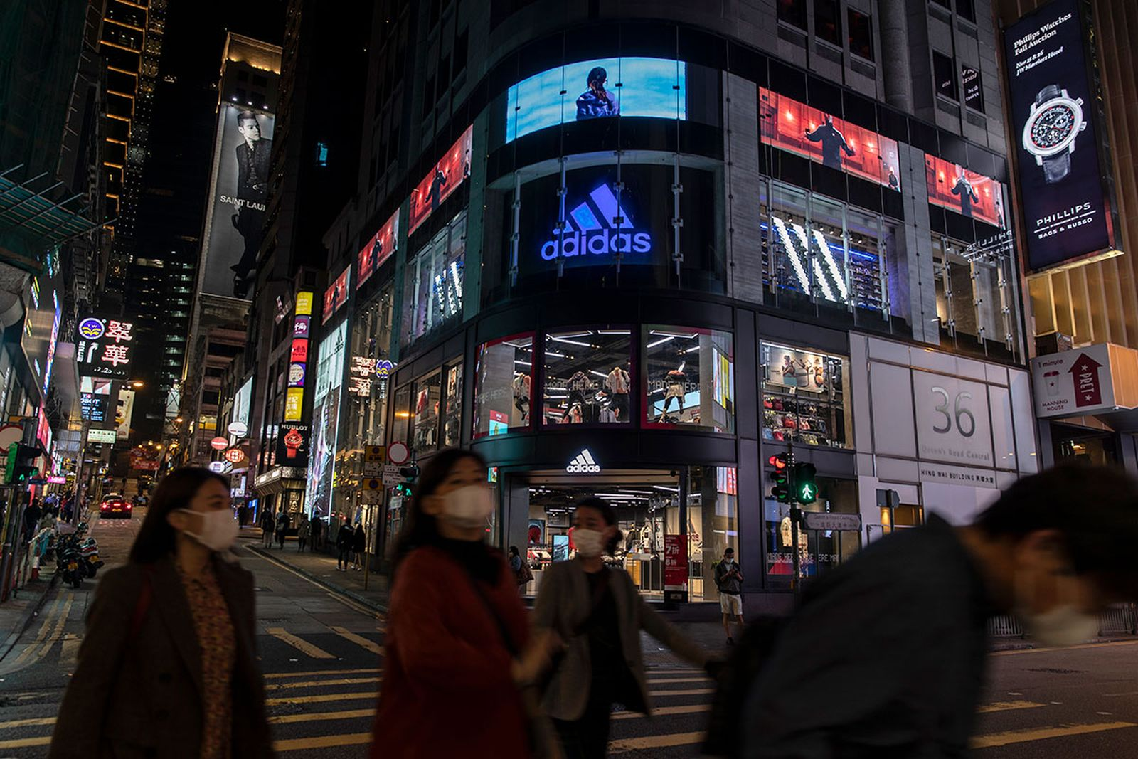 Pedestrians wearing face masks walk past the Adidas store and logo