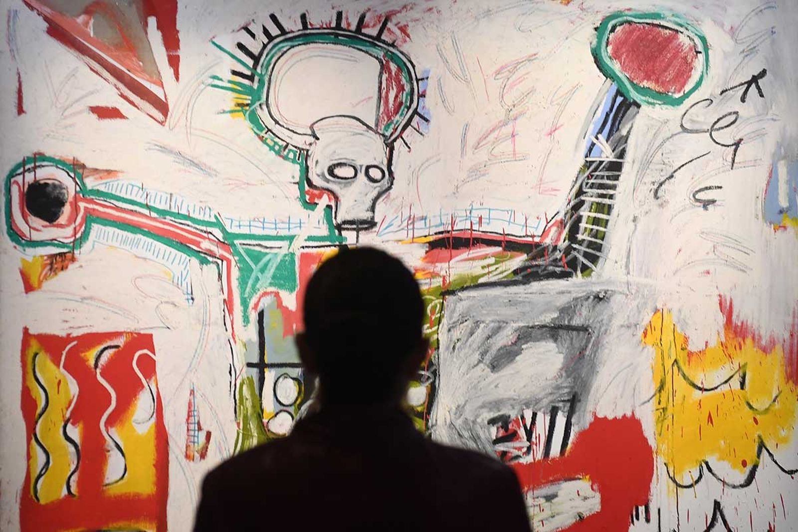 Person looking at Basquiat painting
