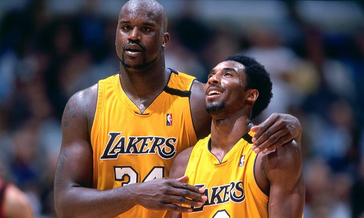Kobe Bryant #8 and Shaquille O'Neal #34 of the Los Angeles Lakers walk and talk during a game