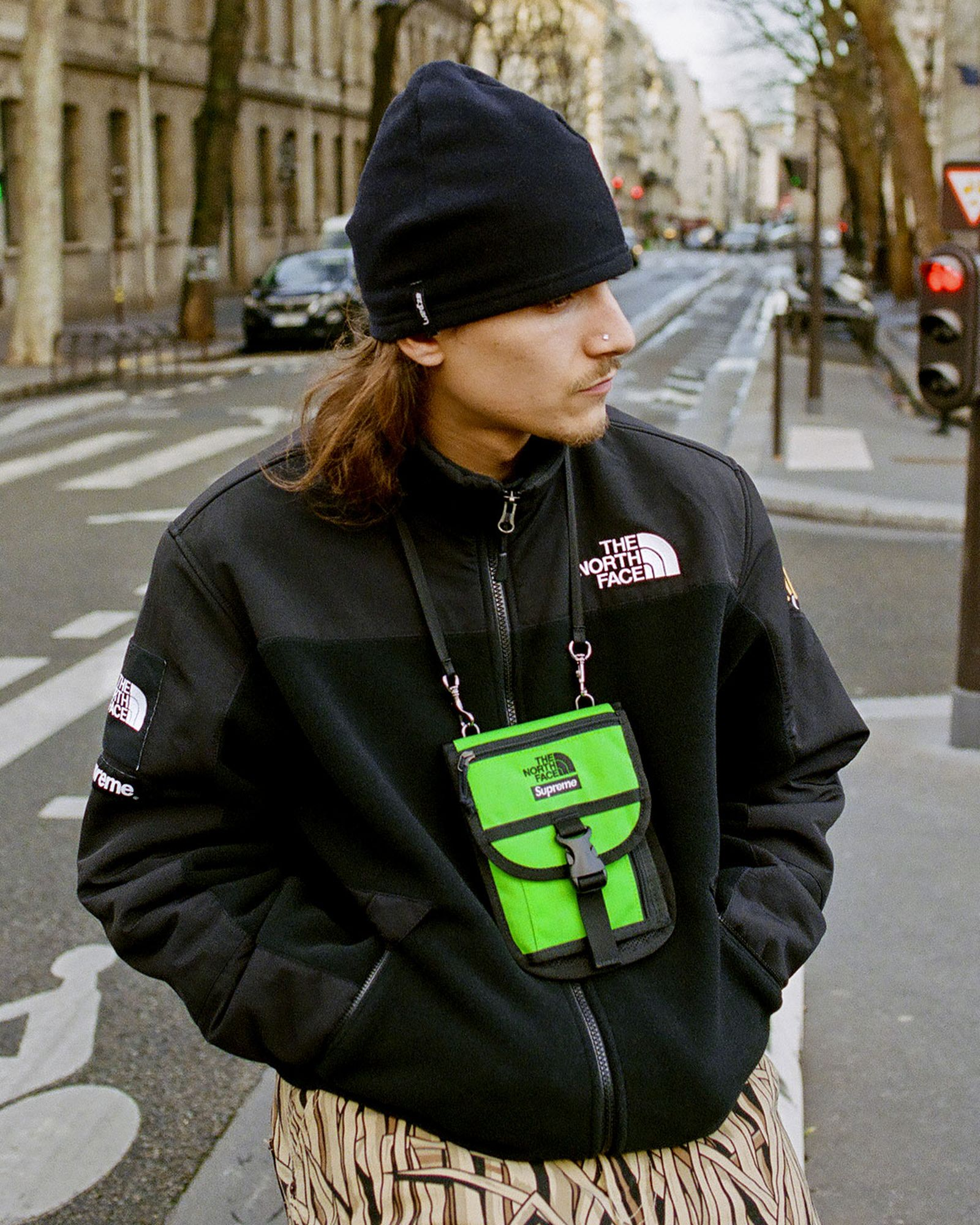Man Wearing Supreme x The North Face RTG Fleece Jacket in Black With Lime Green Bag