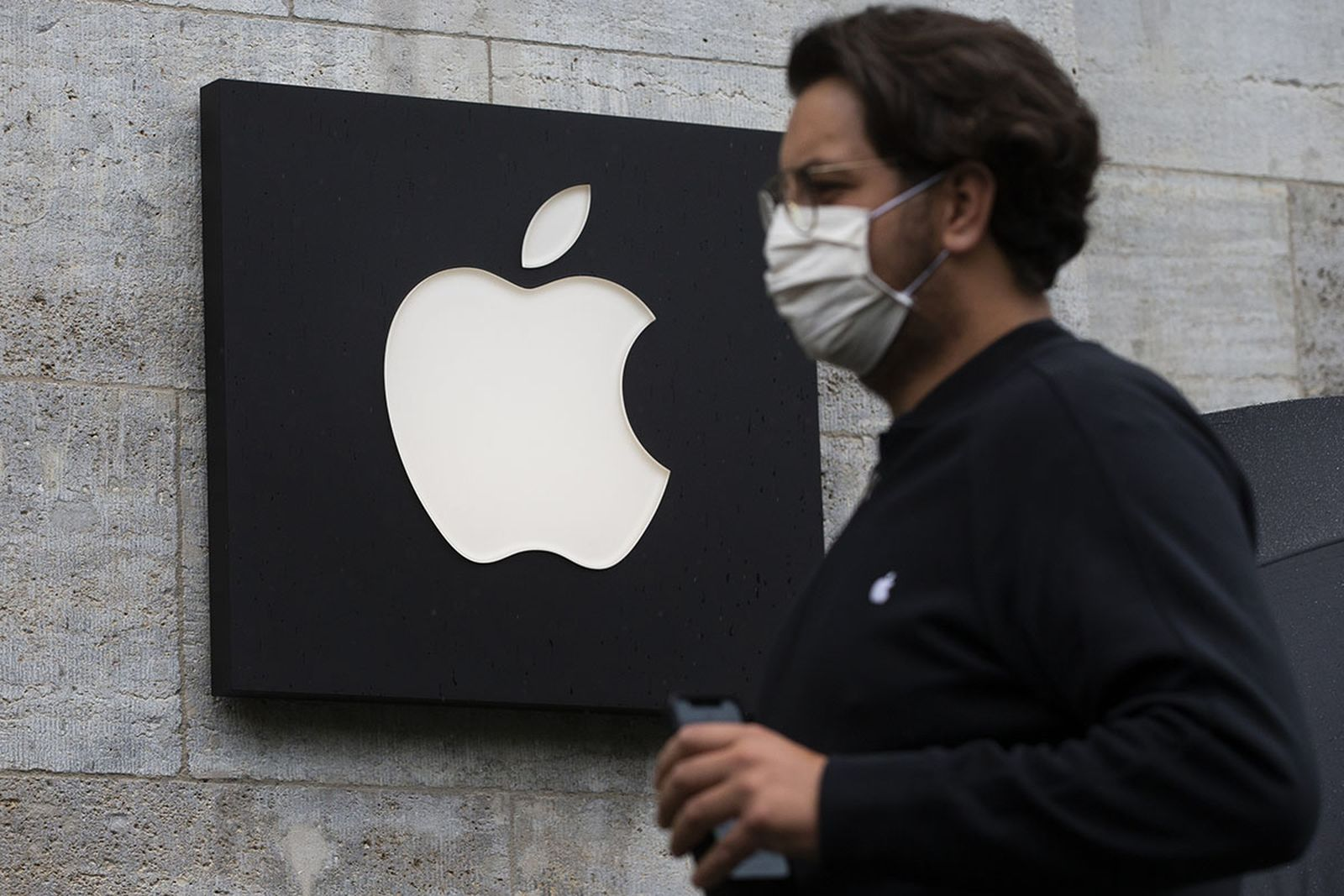 Customers who got appointments wearing medical masks wait to enter Apple Store in Berlin