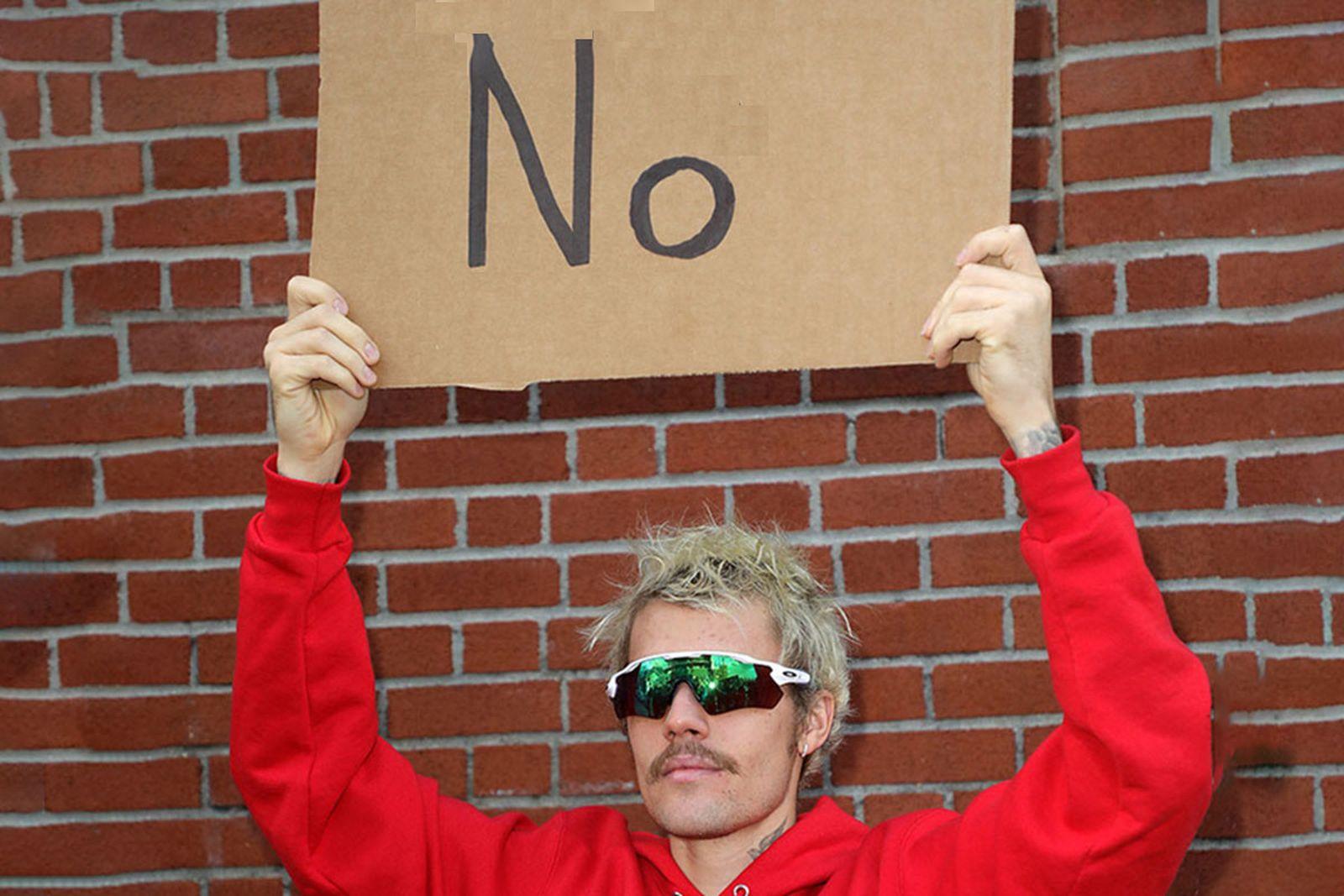 """Justin Bieber holds up """"no"""" sign"""