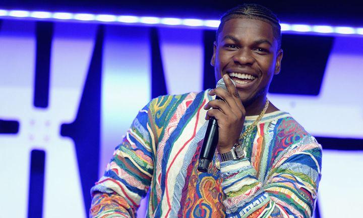 John Boyega on stage holds microphone smiling