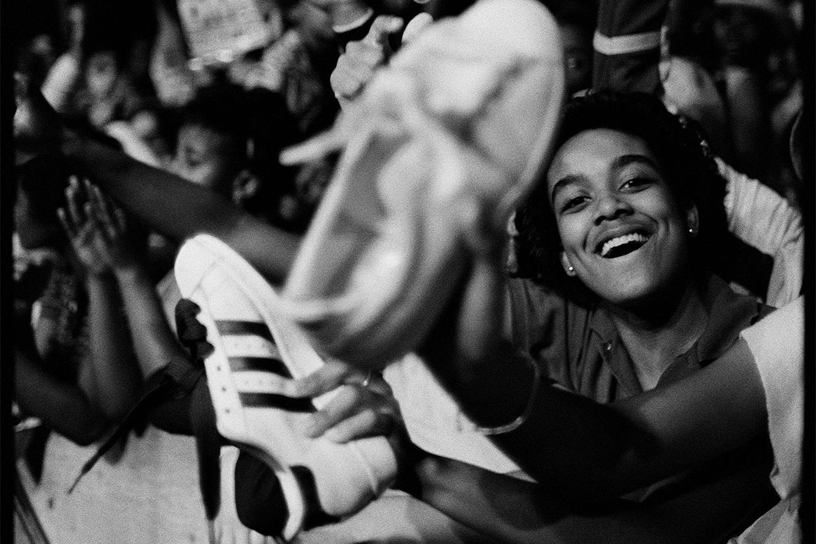 A fan proudly waves his adidas Superstars in the air at a Run-DMC concert.
