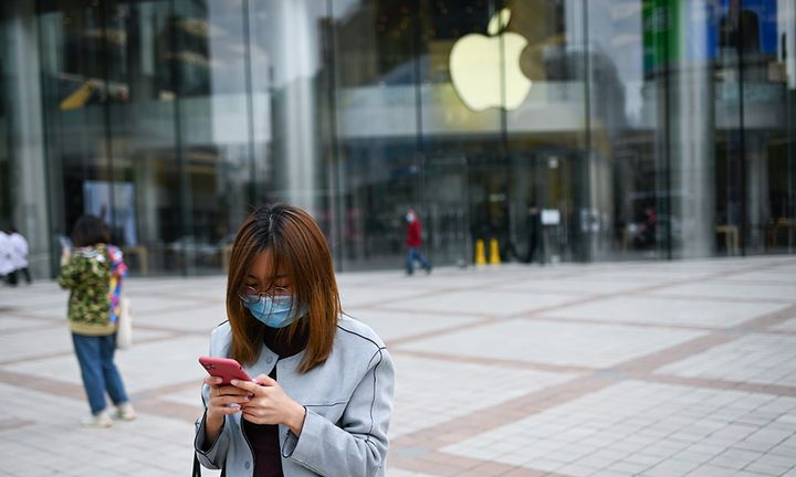 A woman wearing a face mask looks at her mobile phone outside an Apple Store in Beijing