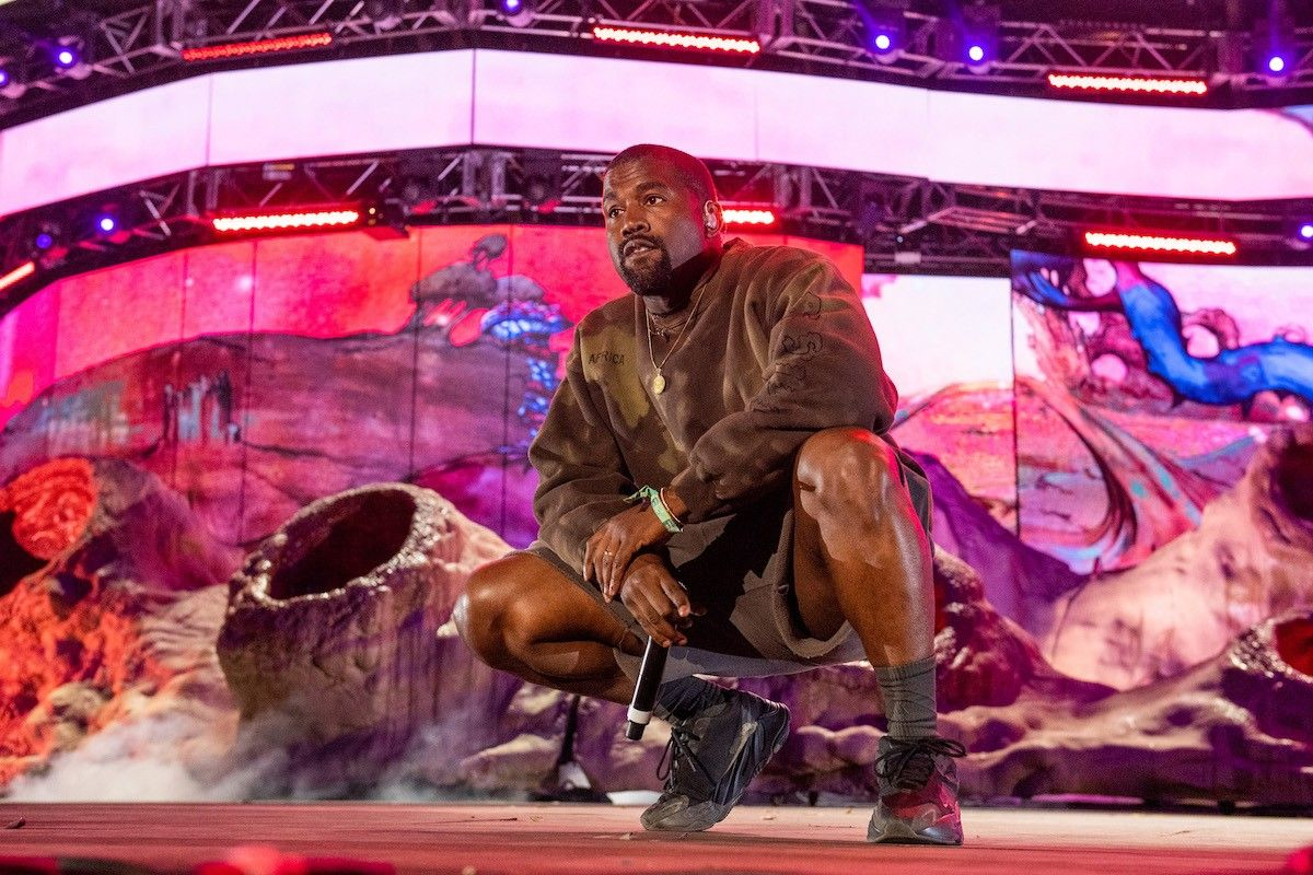 Kanye West squats on stage brown outfit