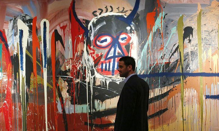 man stands next to the artwork 'Untitled' made by artist Jean-Michel Basquiat