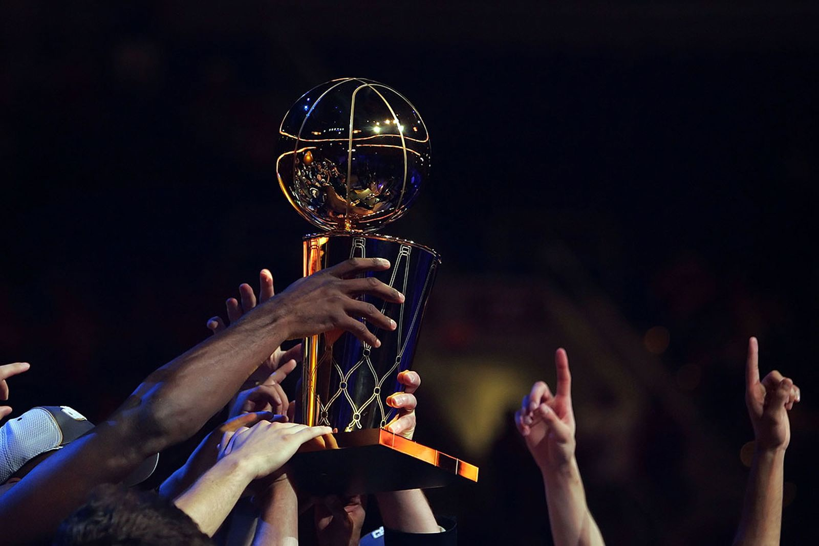 Members of the San Antonio Spurs hold up the Larry O'Brien Championship Trophy after winnin Game Four of the NBA Finals against the Cleveland Cavaliers