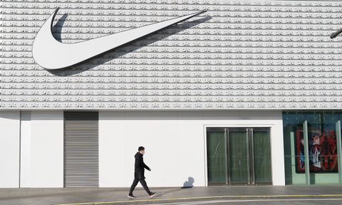 A man wearing a face mask walks past a Nike store in Central Business District, Beijing