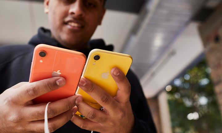 customer holds yellow and orange iPhones in apple store