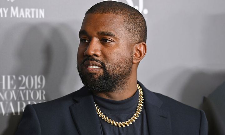 Kanye West black suit gold chain grey background