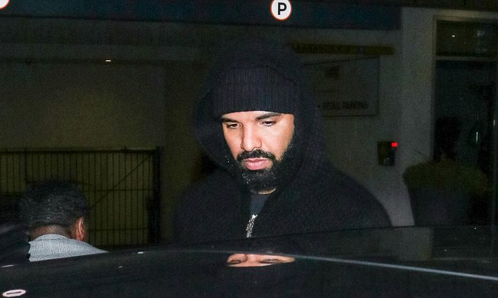 Drake seen stepping into a car with hoodie up