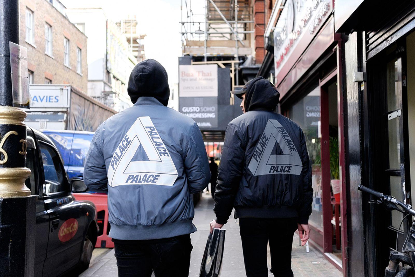 two men walk street wearing palace bombers