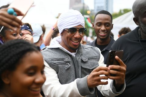 Nick Cannon white turban holds phone amid crowd