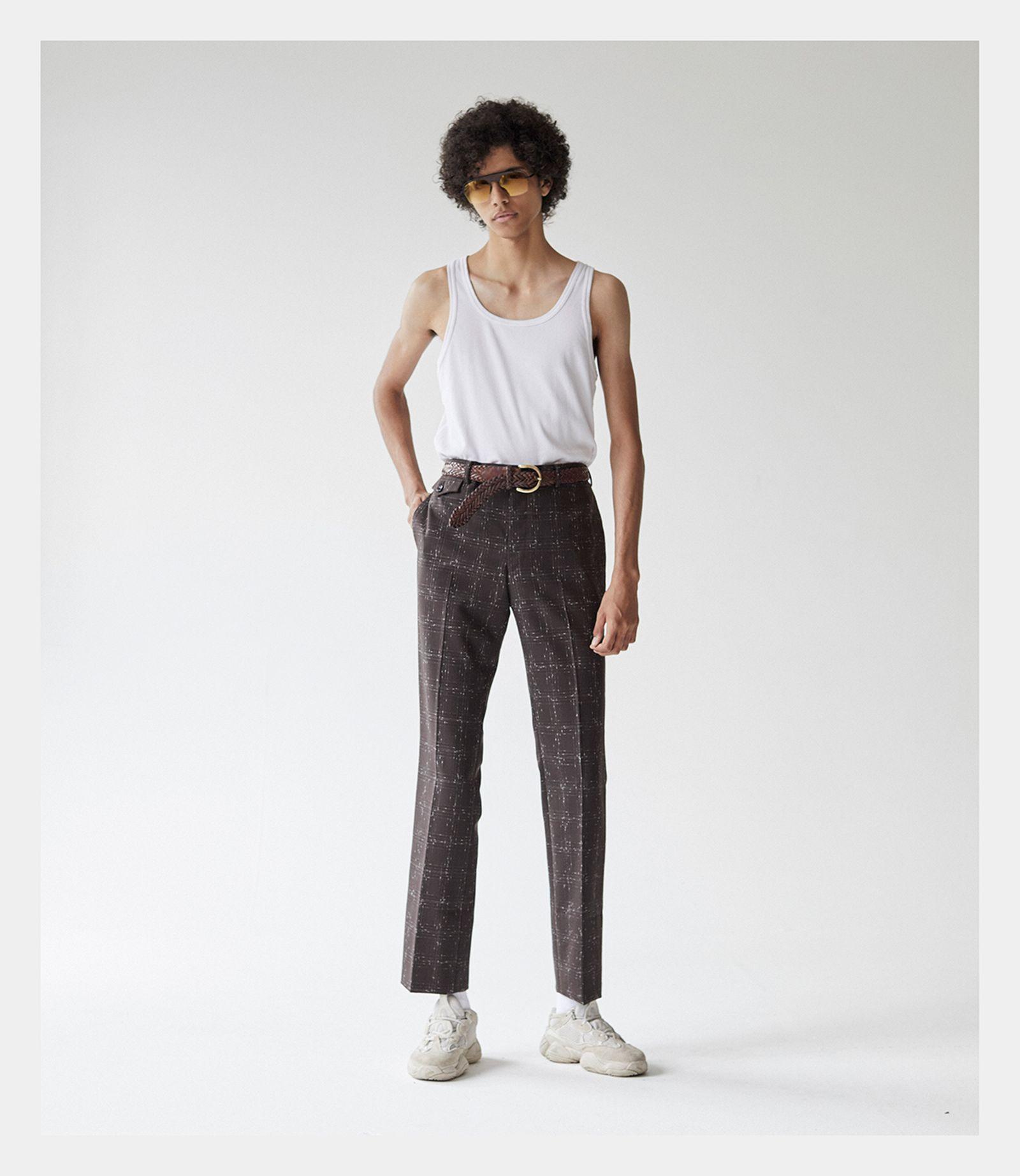 Vest: UNIQLO. Trouser:  JOHN LAWRENCE SULLIVAN. Sneakers: ADIDAS YEEZY DESERT RAT 500 BLUSH. Sunglasses: BELSTAFF Aviators.