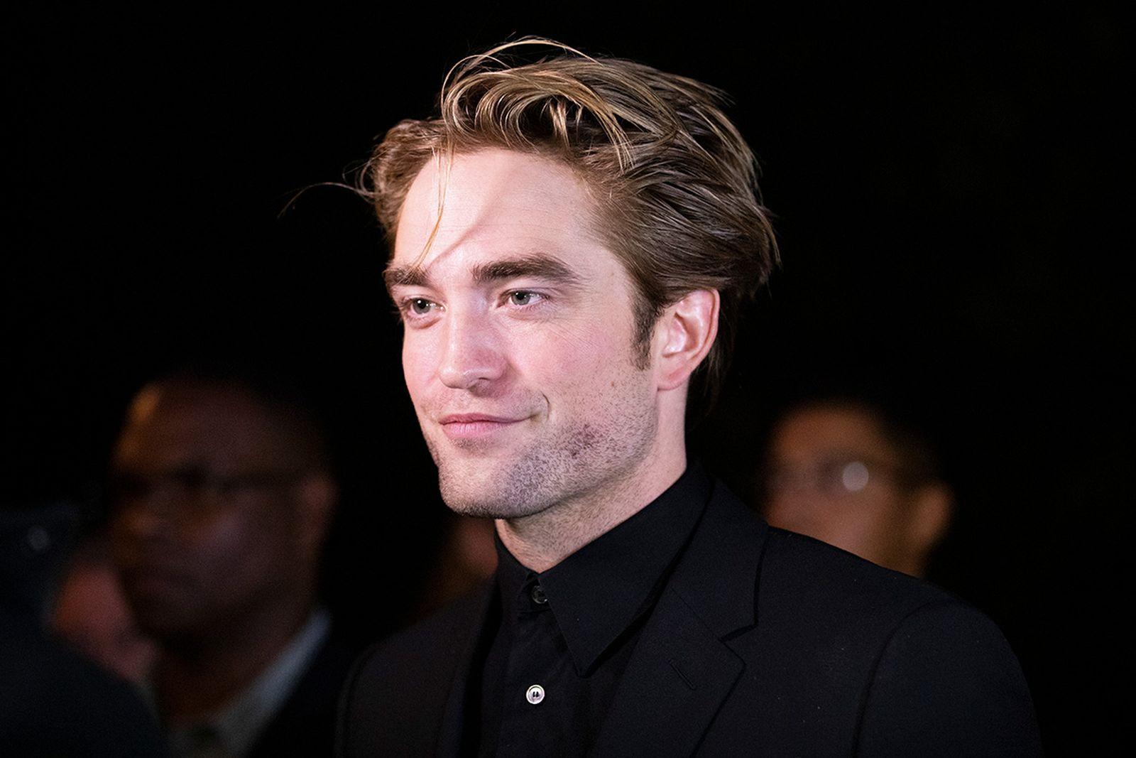 Robert Pattinson on the red carpet, black background