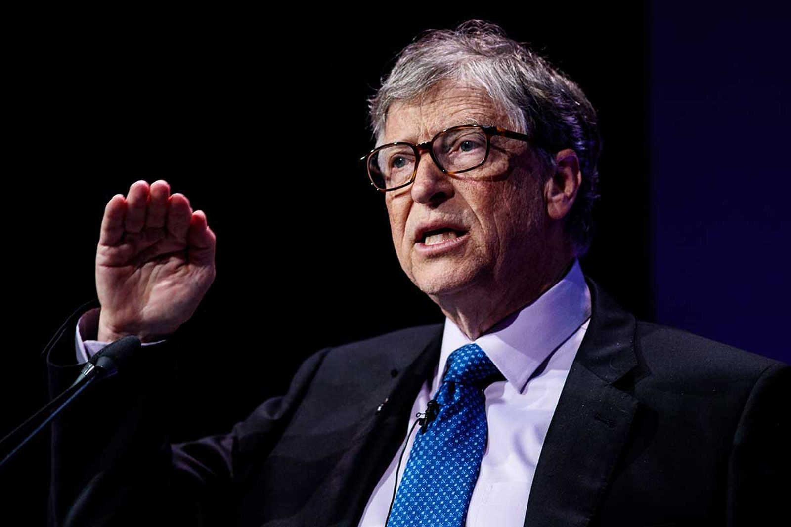Bill Gates giving a speech on stage