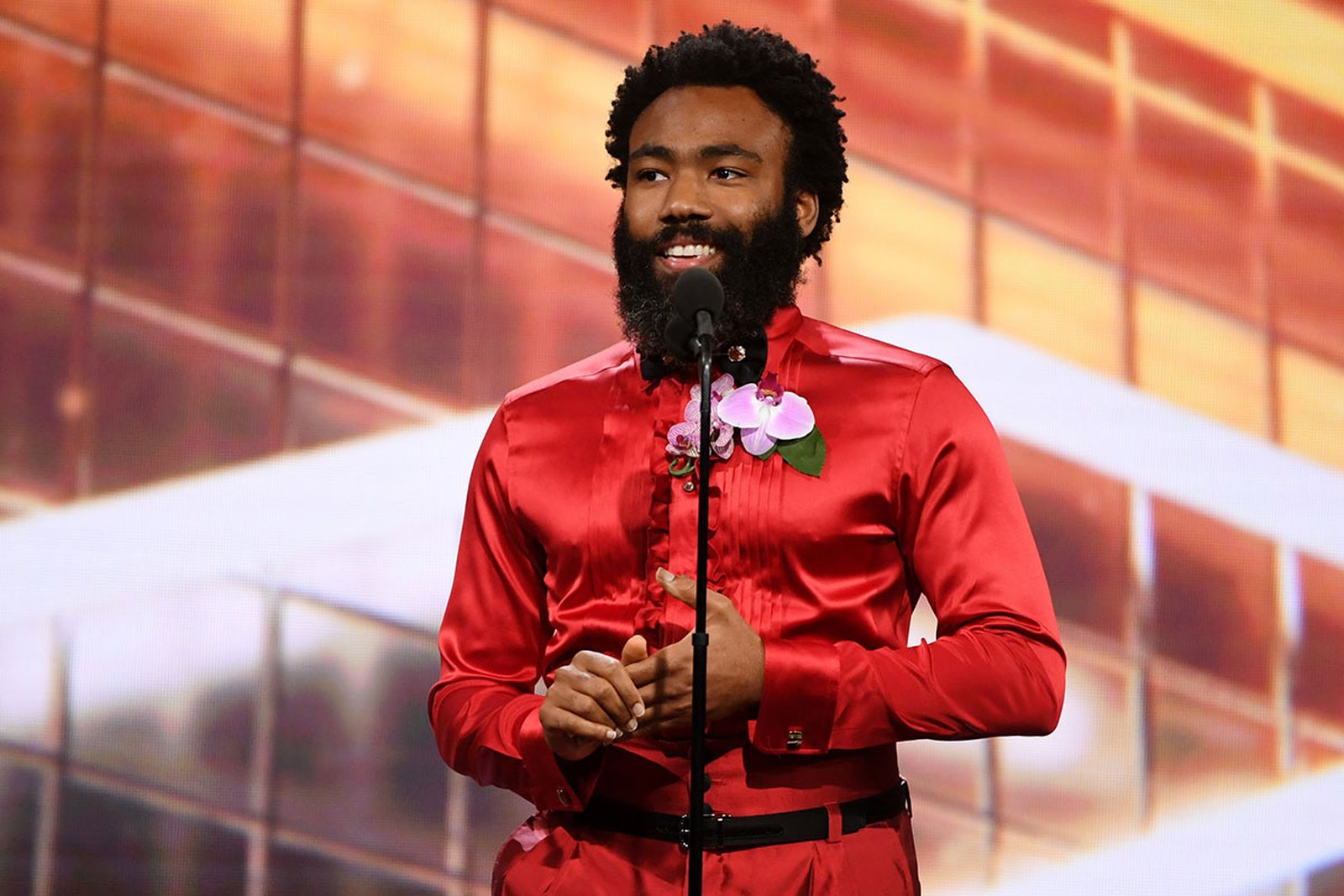 Donald Glover on stage in red outfit