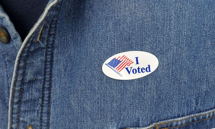 """A voter displays their """"I Voted"""" sticker on their shirt after voting"""