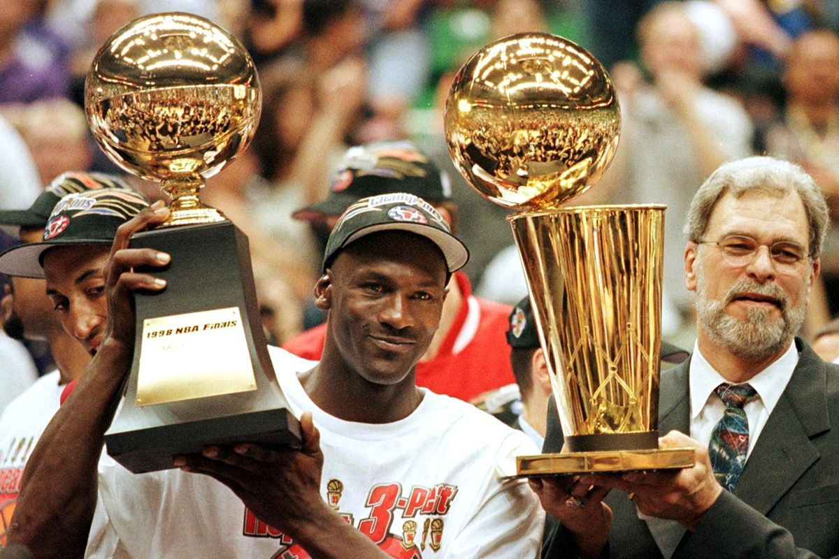 Michael Jordan (L) holds the NBA Finals Most Valuable Player trophy and former Chicago Bulls head coach Phil Jackson holds the NBA champions Larry O'Brian trophy 14 June after winning game six of the NBA Finals with the Utah Jazz at the Delta Center in Salt Lake City, UT.