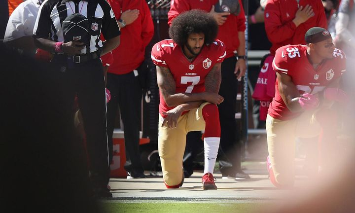 Colin Kaepernick kneels on football field during national anthem