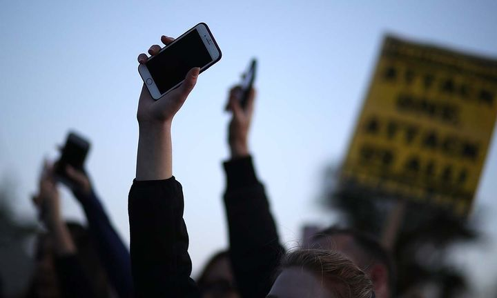 Black Lives Matter protesters hold up their cell phones during a vigil and demonstration