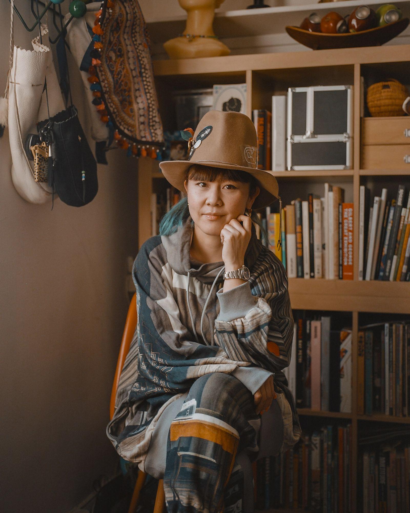 Hitomi Yokoyama wearing a hat sitting indoors in front of a bookshelf