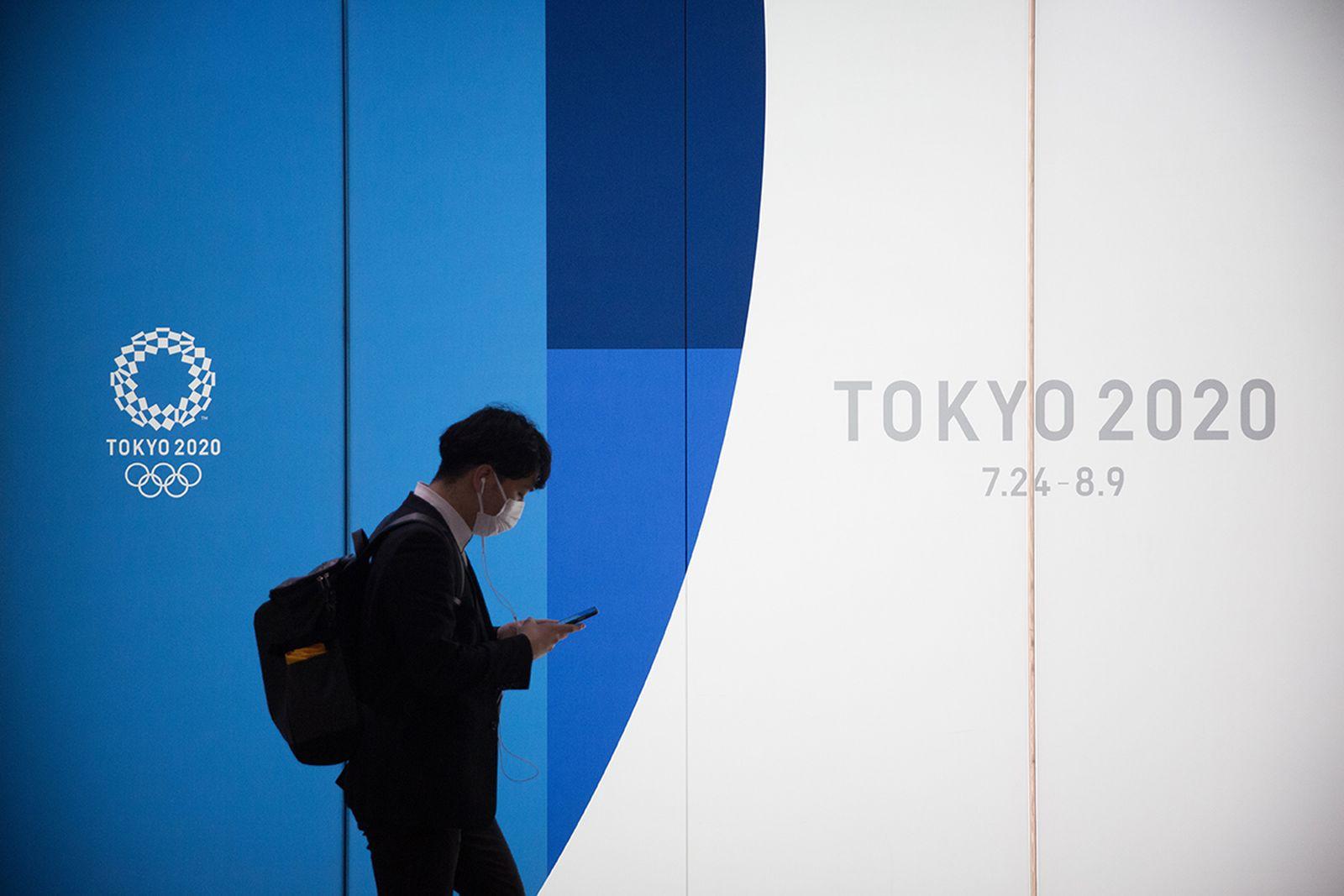 Man wearing face mask walks past billboard for Tokyo olympics