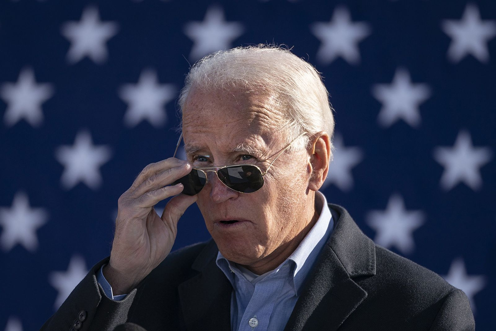 Joe Biden takes off his sunglasses while speaking at a campaign