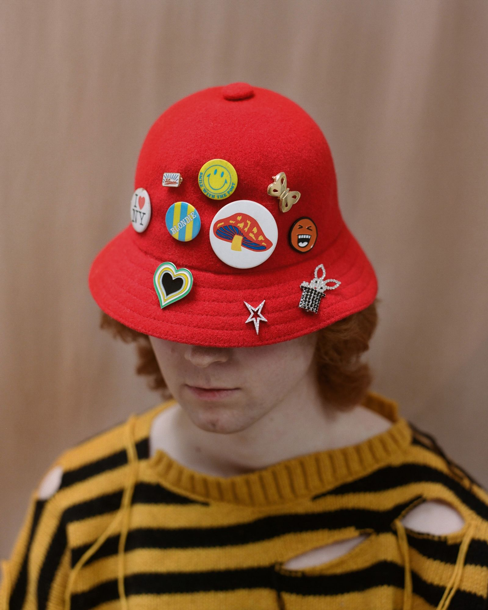 Sweater Charles Jeffrey Loverboy, Hat Kangol, (from left to right) I heart NY pin THE RUSTY PIN, Small enamel pin VISVIM from MR PORTER, Yellow smiley face pin THE RUSTY PIN, Butterfly brooch CONTEMPORARY WARDROBE, Orange smiley face pin DUO LTD, Blondie pin THE RUSTY PIN, Mushroom pin THE RUSTY PIN, Heart pin CONTEMPORARY WARDROBE, Star Earring ALAN CROCETTI, Rabbit in a hat brooch ART SCHOOL from MATCHES UK