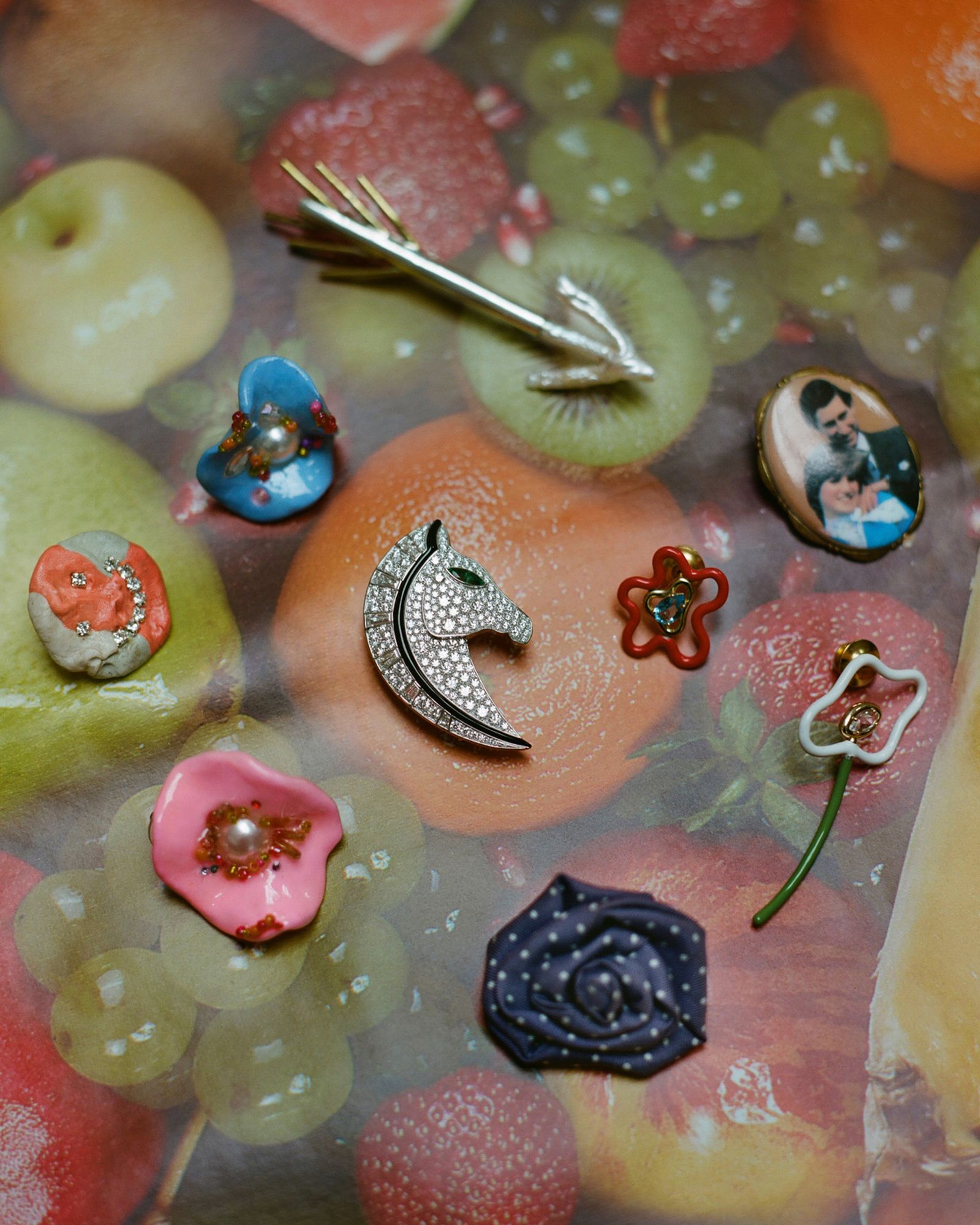 Arrow brooch EMILY FRANCES BARRETT, Cameo brooch CONTEMPORARY WARDROBE, Blue flower earring BLOBB, Smiley brooch CORRINA GOUTOS, Horse brooch BVLGARI, Red floral pin with blue stone BEA BONGIASCA, White and green enamel floral pin BEA BONGIASCA, Pink flower earring BLOBB, Silk floral pin CHARVET